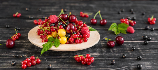Raspberry, cherry, red currant, blackcurrant on a wooden plate against a dark background. It can be used as a background
