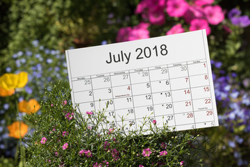 Close-up: calendar with lunar days and holidays is among blooming fresh flowers in a beautiful colorful garden. Concept: July is the middle of flowering summer.