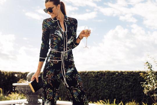 Beautiful woman with wine walking outdoors