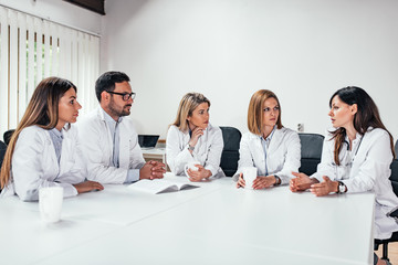 Clinic, people, healthcare and medicine concept. Group of medical staff talking in a meeting.