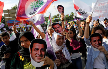 Supporters of Turkey's main pro-Kurdish Peoples' Democratic Party hold masks of their jailed former leader and presidential candidate Selahattin Demirtas during a rally in Ankara