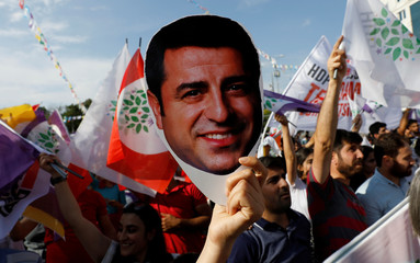 A supporter of Turkey's main pro-Kurdish Peoples' Democratic Party holds a mask of their jailed former leader and presidential candidate Selahattin Demirtas during a rally in Ankara