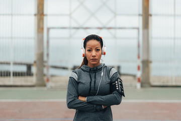 Empowered and confident sporty woman portrait. Female athlete on urban workout wearin headphones.