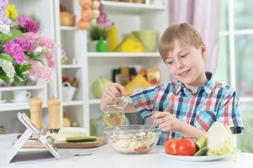 Cute little boy making dinner