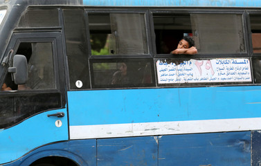 A boy is seen riding a public transport bus in Cairo