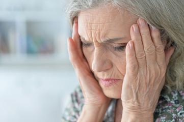 portrait of senior woman with headache