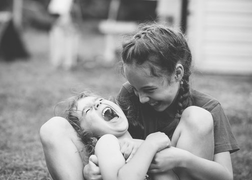 Two Happy little girls laughing and hugging at the  summer park. Black and white photo