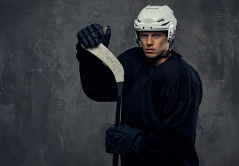 Hockey player wearing black protective gear and white helmet holds a hockey stick on a gray background.