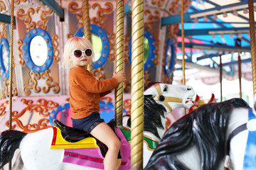 Cute Little Toddler Girl in Big Sunglasses Riding on Carnival Carousal