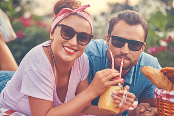 Portrait of a happy middle age couple during romantic dating outdoors, enjoying a picnic while lying on a blanket in the park.