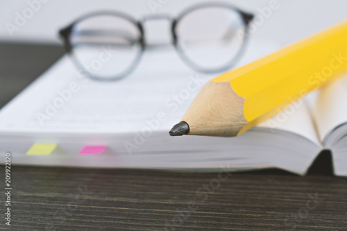 Close Up Of Hipster Glasses For Reading On An Open Book With Big Yellow  Pencil In
