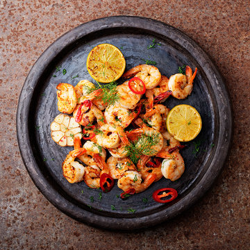 Prawns Shrimps roasted on  pan with lemon and garlic on dark rustic background. top view.