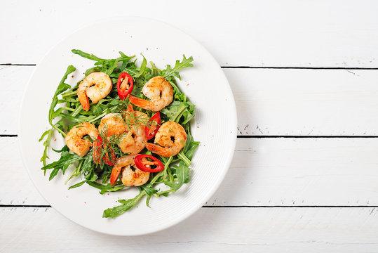 Arugula salad with prawn shrimp on white background. top wiev