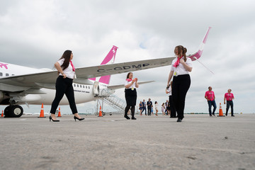 Employees walk on the tarmac during a presentation by WestJet celebrating Canada's first ultra low cost airline, Swoop, at John C. Munro Hamilton International Airport in Hamilton