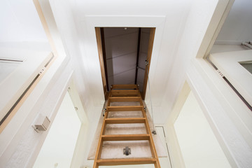 Wooden staircase to the attic in a modern house