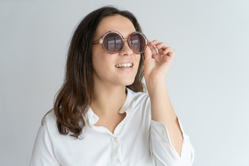 Inspired smiling girl in stylish round sunglasses posing at camera. Closeup of young Caucasian woman touching glasses and looking up. Eye care and summer look concept