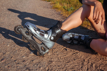 teenage girl rollerblading on the street on the road in the countryside on a summer evening at sunset close-up of a foot with a copy space