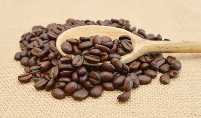 Coffee Beans and wooden spoon in burlap isolated on white.