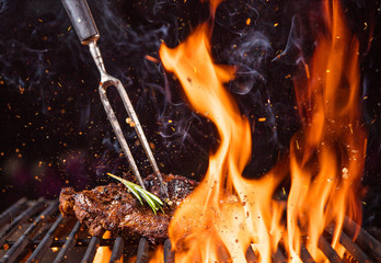 Photo sur Aluminium Grill, Barbecue Beef steak on the grill with flames