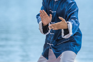 Young man practicing traditional Tai Chi Chuan, Tai Ji and Qi gong in the park for healthy, traditional chinese martial arts concept.