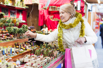 Mature woman choosing decorations at Christmas market