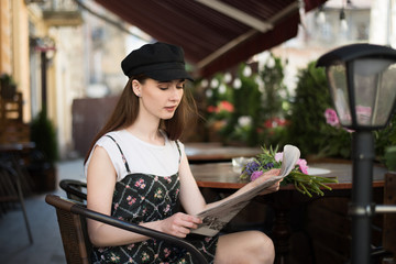 Young woman having a breakfast reading newspaper outdoors at the typical french cafe terrace in France. Playful girl with perfect long hairs posing outdoor. Wearing wool cap. Street fashion look.