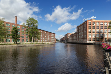 Old red brick industrial buildings along the Tammerkoski rapids in downtown Tampere, Finland on a sunny day. Tampella was an industrial company operating there but now it's a district of the same name