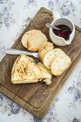 Slice of grilled camembert  with toasted baguettes and cranberry jam