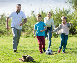 Adult parents with two kids playing soccer