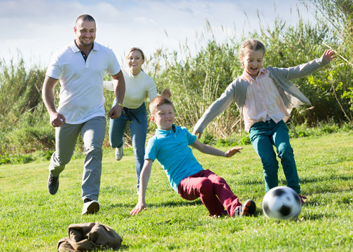 Positive parents with two kids playing soccer