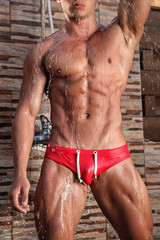 Torso of muscular young sexy wet man in the shower outdoors