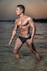 Muscular young sexy wet boy in a underwear posing in the sea at sunset