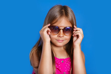 Portrait of young pretty girl in pink dress, sunglasses and hat on blue background . Summer vacation and travel concept
