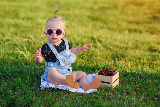 Adorable little girl in stylish pink sunglasses and denim clothes. A girl in a park with a wooden box of fresh fruits.