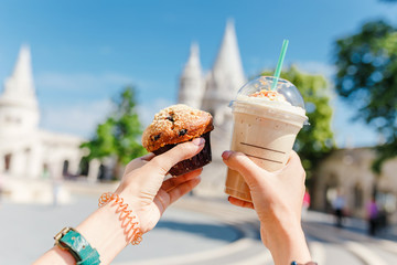 Young asian woman tourist drinking frappe sweet cold coffee and tasty muffin at the Budapest city street near Fisherman Bastion. Travel in Hungary and fast food break concept