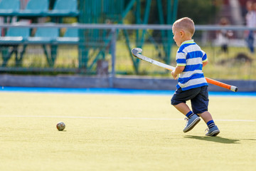 Small funny boy playing field hockey with stick. Concept field hockey image with copy space