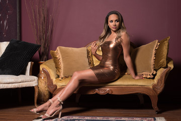 Elegant Woman in a Bronze Dress Sitting on a Vintage Sofa