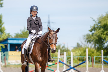 Young girl riding horse on equestrian competition. Equestrian dressage sport background with copy space