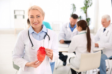 Female doctor holding heart model in clinic. Cardiology center