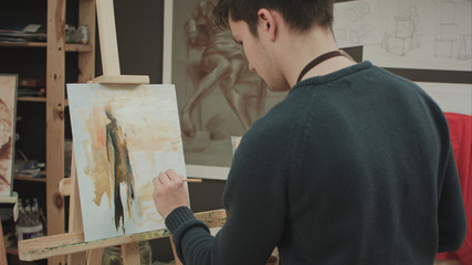 Young student painting picture with oils and holding palette