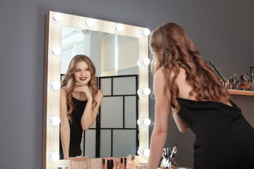 Young beautiful woman near mirror in makeup room