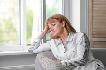 Senior woman suffering from depression on sofa near window