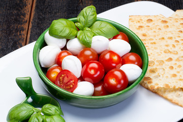 Italian soft cheese, young small balls mozzeralla cheese salad served with fresh basil and tasty ripe cherry tomatoes