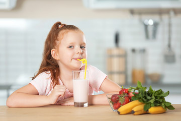Little girl with glass of delicious milk shake in kitchen
