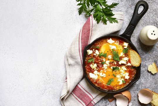 Shakshouka (spicy tomato stew with chicken eggs) with feta cheese - traditional dish of israeli cuisine.Top view with copy space.