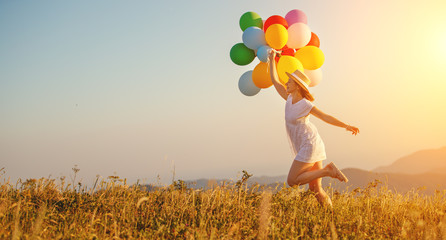 happy woman with balloons at sunset in summer