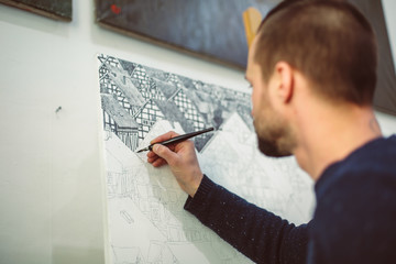 Portrait of male artist drawing houses with a black ink pen on canvas behind