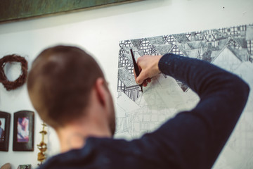 Portrait of male artist drawing with a black pen on big canvas behind in his art studio