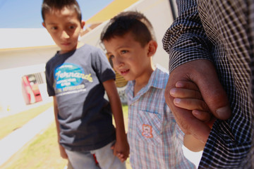 Salvadoran migrant Epigmenio Centeno and his sons pose for a photograph outside the shelter House of the Migrant, after Epigmenio decided to stay with his children in Mexico due to U.S. President Donald Trump's child separation policy, in Ciudad Juarez