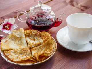 Teapot, a cup,  and pancakes on a plate on a wooden table.